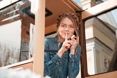 Szczęśliwa kobieta dzwoni od telefonicznego pudełka i pokazuje cisza znaka fotografia royalty free