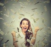 Szczęśliwa kobieta exults pompujący pięści ekstatyczne świętuje sukces pod pieniądze deszczem