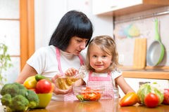 Szczęśliwa kobieta i dziecko przygotowywa zdrowego jedzenie wpólnie Zdjęcia Royalty Free