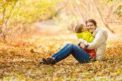 Szczęśliwa kobieta i jej mały syn ma zabawę w jesień parku Obraz Stock