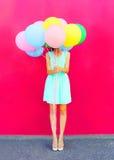 Szczęśliwa kobieta jest kryjówkami jej głowa lotniczy kolorowi balony ma zabawę nad różowym tłem fotografia stock