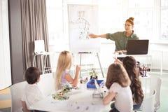 Szczęśliwa kobieta mówi dzieciaków jak robić zabawce obraz royalty free