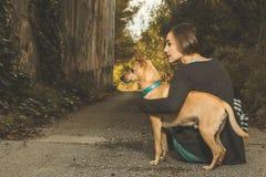 Szczęśliwa kobieta muska jej psa fotografia royalty free