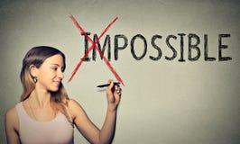 Szczęśliwa kobieta nawraca słowo niemożliwego ewentualny z piórem zdjęcie stock