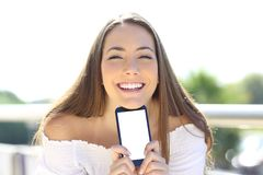 Szczęśliwa kobieta ono uśmiecha się pokazywać smartphone ekran obrazy stock