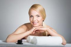 Szczęśliwa kobieta opiera na stole z ręcznikami i zdrojów kamieniami Obraz Royalty Free