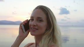 Szczęśliwa kobieta opowiada na telefonie, śmia się na plaży zbiory wideo