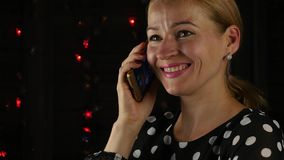 Szczęśliwa kobieta opowiada na telefonie komórkowym i pije wino w zmroku świąteczny atmosfery i świętowania pojęcie 4K zbiory