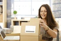 Szczęśliwa kobieta otwiera pocztową paczkę Obrazy Royalty Free