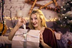 Szczęśliwa kobieta otwiera prezent na nowego roku ` s wigilii zdjęcia stock