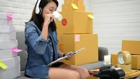 Szczęśliwa kobieta pakuje z pudełka pojęciem w domu z hełmofonami pracuje online rynek zbiory