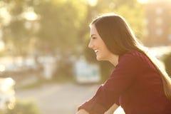 Szczęśliwa kobieta patrzeje daleko od w balkonie Zdjęcia Stock