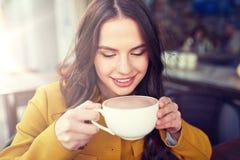 Szczęśliwa kobieta pije kakao przy miasto ulicy kawiarnią zdjęcia stock