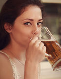 Szczęśliwa kobieta pije piwo od dużego szkła Fotografia Royalty Free