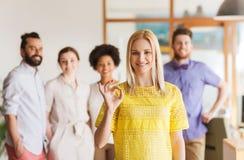 Szczęśliwa kobieta pokazuje ok nad kreatywnie biuro drużyną fotografia royalty free