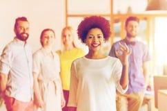 Szczęśliwa kobieta pokazuje ok nad kreatywnie biuro drużyną zdjęcia royalty free