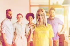 Szczęśliwa kobieta pokazuje ok nad kreatywnie biuro drużyną obraz stock
