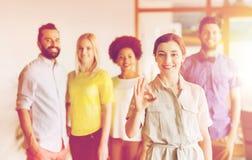 Szczęśliwa kobieta pokazuje ok nad kreatywnie biuro drużyną obraz royalty free