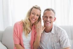 Szczęśliwa kobieta pokazuje pierścionek zaręczynowego oprócz mężczyzna Obraz Royalty Free