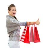 Szczęśliwa kobieta pokazywać aprobaty z torba na zakupy zdjęcia stock