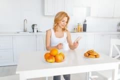 Szczęśliwa kobieta przy stołem z owoc i pieczeniem fotografia stock