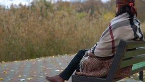 Szczęśliwa kobieta relaksuje na ławce w parku zbiory wideo