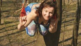 Szczęśliwa kobieta robi fizycznym ćwiczeniom na arkanach outdoors zbiory