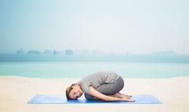Szczęśliwa kobieta robi joga w dziecko pozie na macie Obrazy Stock