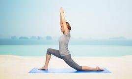 Szczęśliwa kobieta robi joga w niskim lunge na macie Zdjęcia Stock