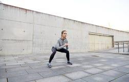 Szczęśliwa kobieta robi kucnięciom i ćwiczy outdoors Obraz Royalty Free