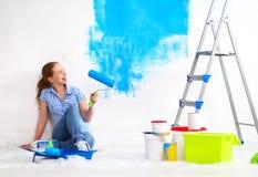 Szczęśliwa kobieta robi naprawom, farby ściana w domu zdjęcie royalty free