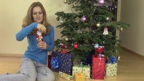 Szczęśliwa kobieta rozwija się Bożenarodzeniowego Santa czekoladowego pobliskiego jedlinowego drzewa zbiory