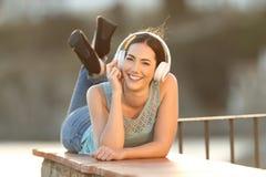 Szczęśliwa kobieta słucha muzyczna patrzeje kamera fotografia stock