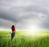Szczęśliwa kobieta skacze w traw polach i raincloud Zdjęcie Stock