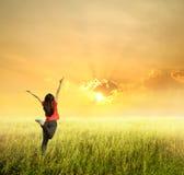 Szczęśliwa kobieta skacze w trawa zmierzchu i polach Zdjęcie Royalty Free