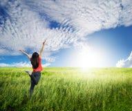 Szczęśliwa kobieta skacze w trawy niebieskim niebie i polach Zdjęcie Royalty Free