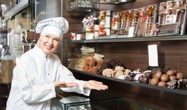 Szczęśliwa kobieta sprzedaje wyśmienicie czekolady zdjęcia royalty free