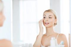 Szczęśliwa kobieta stosuje śmietankę twarz przy łazienką Zdjęcie Royalty Free