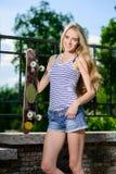 Szczęśliwa kobieta trzyma jej deskorolka outdoors Fotografia Stock