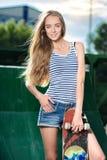Szczęśliwa kobieta trzyma jej deskorolka outdoors Obraz Stock