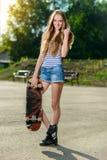 szczęśliwa kobieta trzyma jej deskorolka outdoors Zdjęcia Royalty Free