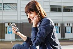 Szczęśliwa kobieta trzyma mądrze telefon słucha muzyka obraz royalty free