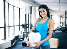Szczęśliwa kobieta trzyma plastikowego zbiornika z sporta odżywianiem Zdjęcia Stock