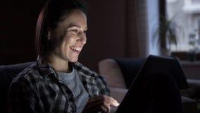 Szczęśliwa kobieta używa cyfrową pastylkę przy nocą zbiory