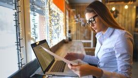Szczęśliwa kobieta używa laptop przy kawiarnią Młody piękny dziewczyny obsiadanie w działaniu na komputerze i sklep z kawą zbiory