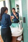 Szczęśliwa kobieta używa prochową makijażu muśnięcia łazienkę Fotografia Royalty Free