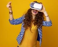 Szczęśliwa kobieta używa rzeczywistości wirtualnej przekładnię i chapiący palec Obrazy Royalty Free