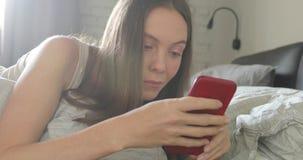 Szczęśliwa kobieta używa smartphone na łóżku w domu zbiory