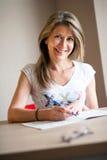Szczęśliwa kobieta uzupełnia crossword łamigłówki zdjęcie royalty free