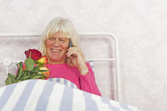 Szczęśliwa kobieta w łóżku z różami i telefonem Obrazy Royalty Free